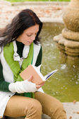 Autumn fountain young woman read book — Stock Photo