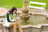 Autumn park fountain young woman read book — Foto Stock