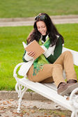 Autumn park bench young woman read book — Stok fotoğraf