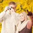 Autumn couple take photo camera in park — Stock Photo