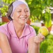 Senior sportive womsmile eat apple outdoor — Stock Photo #7700143
