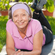 Senior sportive woman listen music on mat - Stock Photo