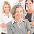 Businesswoman senior with colleagues in the back — Stock Photo