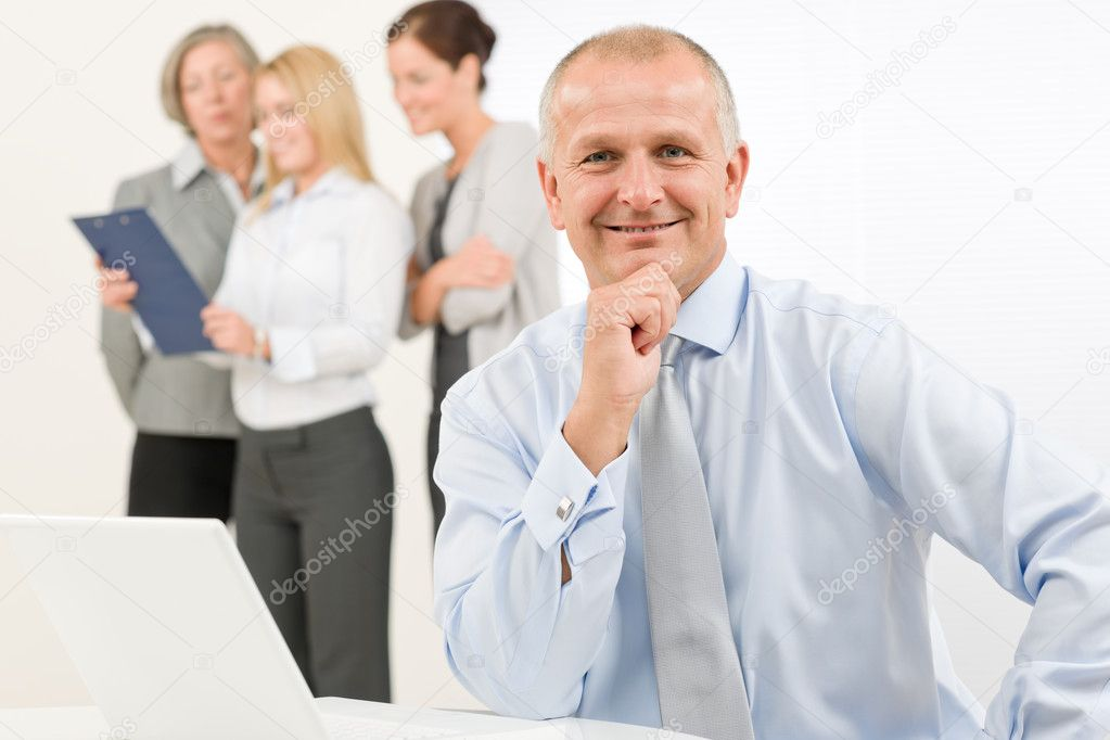 Business team happy mature businessman with attractive colleagues looking file  Stock Photo #7735839