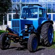 Painted in blue tractor standing before building - Stock Photo