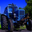 Painted in blue tractor standing before building — Stock Photo #6818113