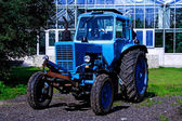 Painted in blue tractor standing before building — Stock Photo