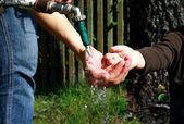 Washing ditrty hands under water stream — Stock Photo
