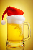 Beer and hat of Santa Claus on a yellow background — Stock Photo