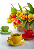 Colorful cups with tea and tulips — Stock Photo