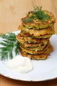 Zucchini fritters with sour cream — Stock Photo