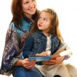 Stock Photo: Merry mother and little girl reading book.