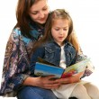 Young woman reads a book a little girl. — Stock Photo