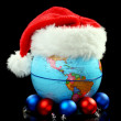 Globe Santa hat and Christmas balls. — Stock Photo