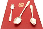 Threes silver spoons on red — Stock Photo