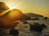 The sun ascends because of a rock over the sea — Stock Photo