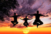 Jumping Yoga silhouettes in lotus — Stock Photo