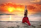 Yoga virabhadrasana warrior pose at sunset — Stock Photo