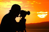 Photographer silhouette at sunset — Stock Photo