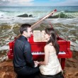 Couple near the piano on the beach — Stock Photo