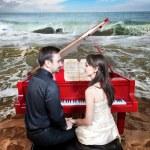 Couple near the piano on the beach — Stock Photo