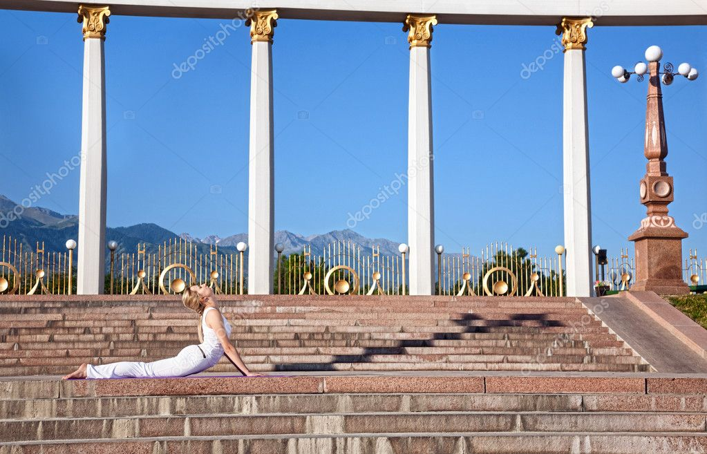 Beautiful Caucasian woman in white cloth doing bhujangasana cobra pose, sixth step of surya namaskar sun salutation Exercise. Woman laying in prone position on  — Stock Photo #6927888