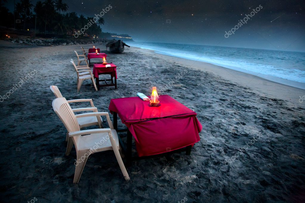 Romantic tropical café on the beach near the ocean. Tables with pink covers illuminated by candles and stars falling at night sky background  — Stok fotoğraf #6927961