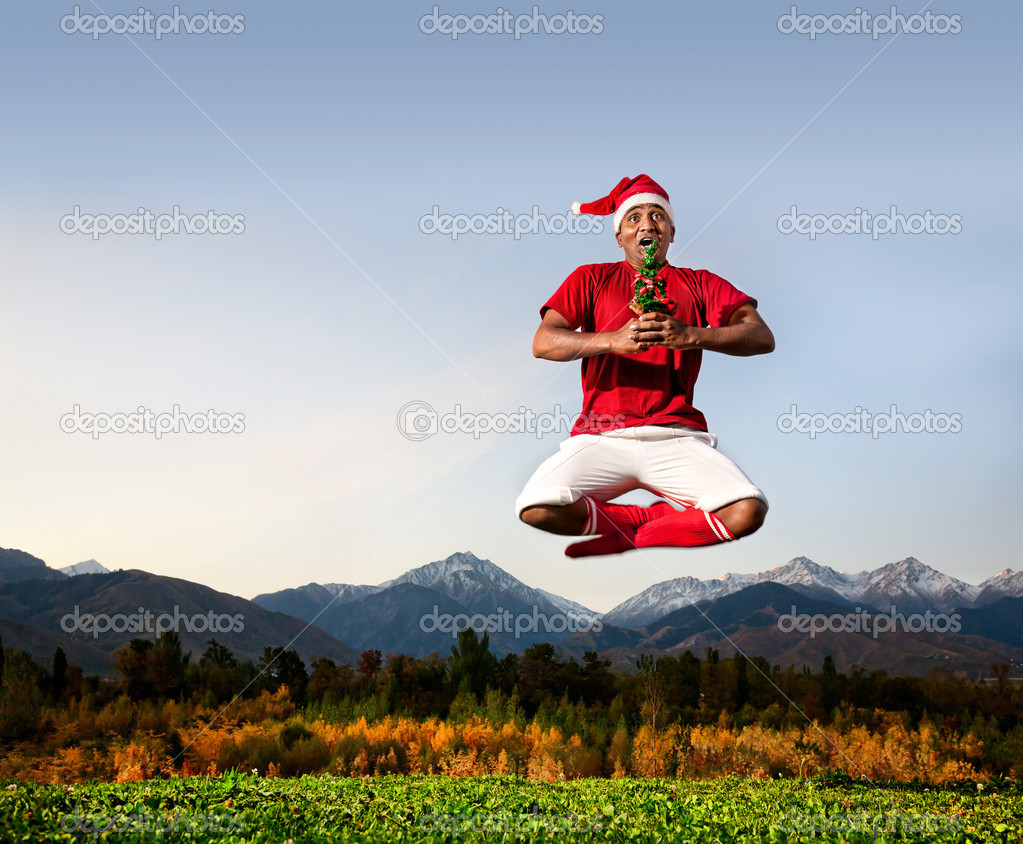 Jumping yoga by Indian man in padmasana lotus pose with Christmas tree in white trousers, red socks and Christmas hat at mountain background. Free space for tex  Stock Photo #7085966