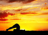 Yoga silhouette Halasana plough pose — Stock Photo