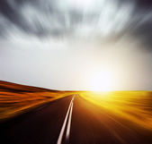 Blured road and blured sky with sun — Stock Photo