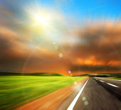 Road and blured sky with sun — Stock Photo