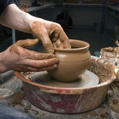 The hands of a potter, creating an earthen jar on the circle — Stock Photo