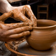 Hands of a potter, creating an earthen jar on the circle — Stock Photo #7943823