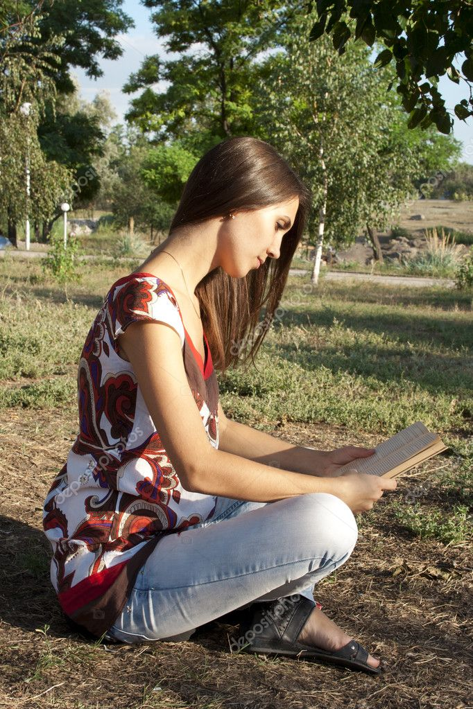 Adult girl reading a book outdoors — Stock Photo #7239008