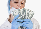 Female doctor holding money — Stock Photo