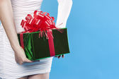 Santa girl hiding a present gifts — Stock Photo
