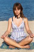 Young beautiful girl practices yoga on the beach — Stock Photo