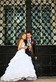 Young Wedding couple stand near huge gate — Stock Photo