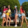 Four sexy pin-up woman near car with graffiti — Stock Photo