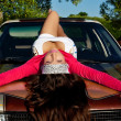 Beauty young girl lay on car at summer sunset — Stock Photo