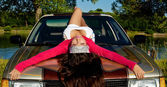 Beauty young girl lay on car at summer sunset — Zdjęcie stockowe