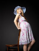 Blond pregnant woman portrait in straw hat — Stock Photo