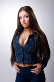 Sexy young brunette posing in jeans costume — Stock Photo
