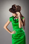 Woman posing in green dress and hair style hat — Stock Photo