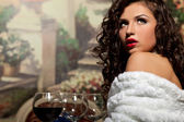 Sexy girl sit with wine in fur coat at evening — Stock Photo