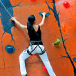 Girl climbing on a climbing wall — 图库照片