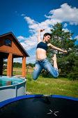 Chica salta sobre una cama elástica — Foto de Stock