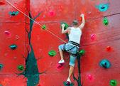 Strong man climbing on a climbing wall — Stock Photo