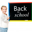 Little girl standing near blackboard — Stock Photo