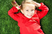 Little girl smiling on grass — Stock Photo